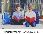 Boys Reading Books Sitting On...