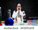 shocked girl at her laboratory  | Shutterstock . vector #692091655