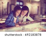 Small photo of Glad mother and daughter exploring expositions of previous centuries in museum