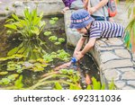 young boy feeding koi fish with ... | Shutterstock . vector #692311036