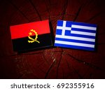 Small photo of Angolan flag with Greek flag on a tree stump isolated