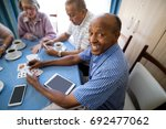 happy senior man playing cards... | Shutterstock . vector #692477062