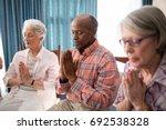 Senior Man Amidst Women Prayin...