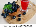 a glass of juice and grapes | Shutterstock . vector #692585302