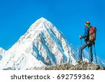 hiker with backpacks reaches... | Shutterstock . vector #692759362