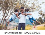 asian father carrying two child ... | Shutterstock . vector #692762428