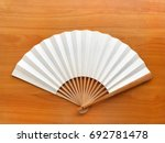 Small photo of Fan white paper Of Chinese or Japanese Made of bamboo, folded on wooden floor and space for letters or symbols with doctrines, philosophy, art, culture, verse, proverbs, Asian uses.
