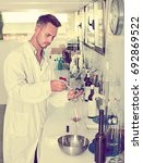 Small photo of Young man in white coat checking wine acidity and sugar saturation in chemical laboratory on a winery