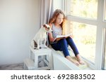 child reading book at home.... | Shutterstock . vector #692883502