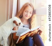 child with dog reading book at... | Shutterstock . vector #692883508
