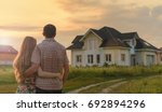 Small photo of couple looking on house