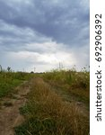 Small photo of Beautiful rain clouds over the field. Summer grass in the field. Rustic landscape with ground road through afield in summer day.