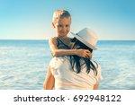 day summer beach.a mother of 36 ... | Shutterstock . vector #692948122