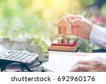 house placed on coins men's...   Shutterstock . vector #692960176