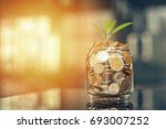 plant growing out of coins with ... | Shutterstock . vector #693007252