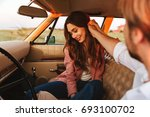 Stock photo young man flirting with his smiling girlfriend by touching her hair and holding her hand while 693100702