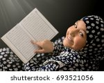 muslim girl reading quran on... | Shutterstock . vector #693521056