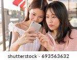 chinese girls playing phone | Shutterstock . vector #693563632