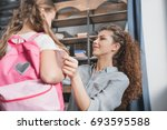 Small photo of beautiful young mother preparing her little daughter for school
