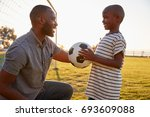 a boy holds a football while... | Shutterstock . vector #693609088