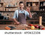 handsome young man in apron... | Shutterstock . vector #693612106