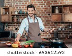 happy young man cooking with... | Shutterstock . vector #693612592