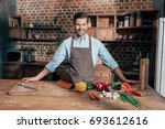 handsome young man in apron on... | Shutterstock . vector #693612616