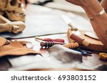 man working with leather using... | Shutterstock . vector #693803152
