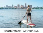 a girl is riding a board on a... | Shutterstock . vector #693904666