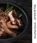 Small photo of Meat ribs sliced in plate with a spicy sauce marinade with honey and herbs on dark wooden background. Top side view.