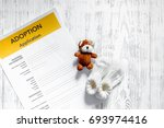 Small photo of Adoption application near toy on light wooden table background top view copyspace
