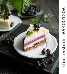 Small photo of A modern mousse cake with a crusty nut layer, a layer of black wild currant and a mousse of white chocolate and yogurt. The cake is decorated with fresh currant berries and leaves of white chocolate