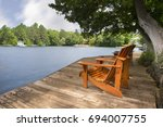 muskoka chairs sitting on a... | Shutterstock . vector #694007755