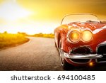 retro car on road and golden... | Shutterstock . vector #694100485