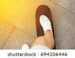 legs with white sneakers on a... | Shutterstock . vector #694106446