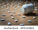 Small photo of Drug addiction, medical abuse and narcotics hook and dependence concept. Empty tablet bottle surrounded by many pills on the floor. Overdose of medicine. Depression and problem.
