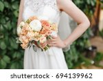 wedding bouquet in bride hands | Shutterstock . vector #694139962