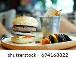 hamburger in a wooden plate | Shutterstock . vector #694168822
