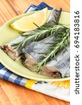 Small photo of Fresh hake fish with rosemary and lemon on the plate.