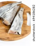 Small photo of Fresh sliced hake fish filets on the cuting wooden board.
