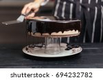 glazing chocolate mousse cake ... | Shutterstock . vector #694232782