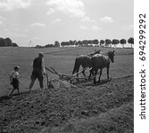 Small photo of Farmer with horses plowing field