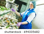 Stock photo buffet female worker servicing food in cafeteria 694335682