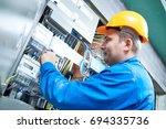 electrician installing energy... | Shutterstock . vector #694335736