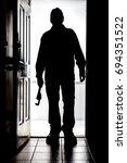 Small photo of Intruder standing at doorway threshold, in silhouette with pipe wrench