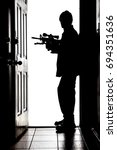 Small photo of Intruder standing at doorway threshold, in silhouette with AR-15 rifle
