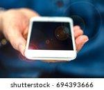female hand holding a white... | Shutterstock . vector #694393666