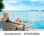 women wear hat sitting on a... | Shutterstock . vector #694454866