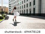 brunette in white dress dancing ... | Shutterstock . vector #694478128