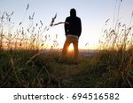 a man standing in the grass and ... | Shutterstock . vector #694516582